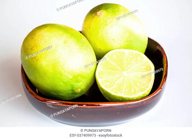 Fresh limes whole and slice in ceramic bowl