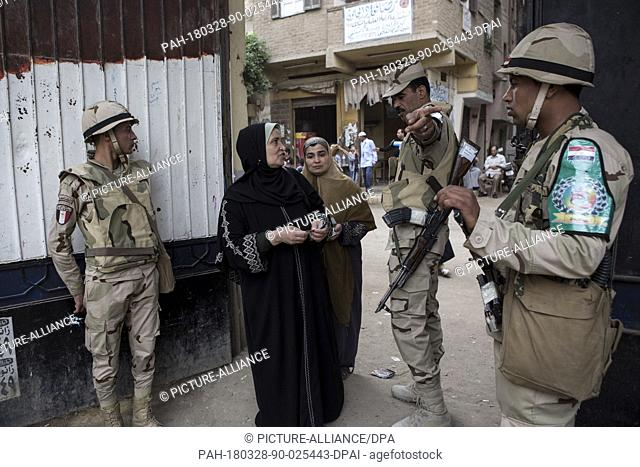 dpatop - An army officer assists an Egyptian woman with directions at the entrance of a polling station on the 3rd day of the 2018 Egyptian presidential...