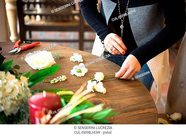 Woman arranging flower heads and stems on wooden table, mid section