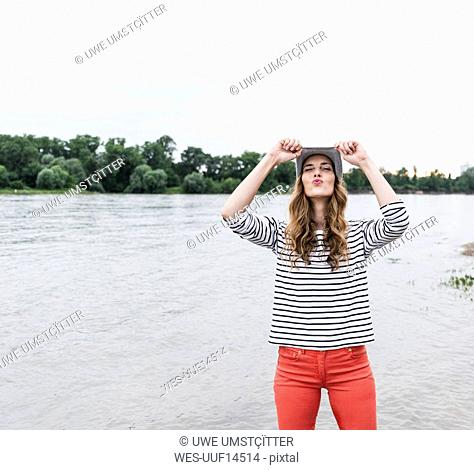 Playful woman wearing wooly hat at a river pouting