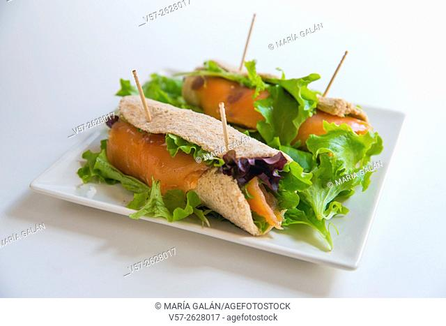 Smoked salmon with lettuce in rolled bread. Close view