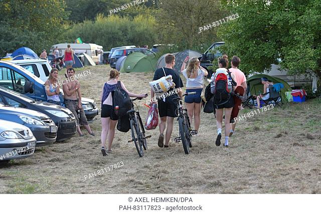 Visitors of the open air music festival 'Jamel rockt den Foerster' - Rock music against right-wing extremism - walk across the camping grounds of the festival...