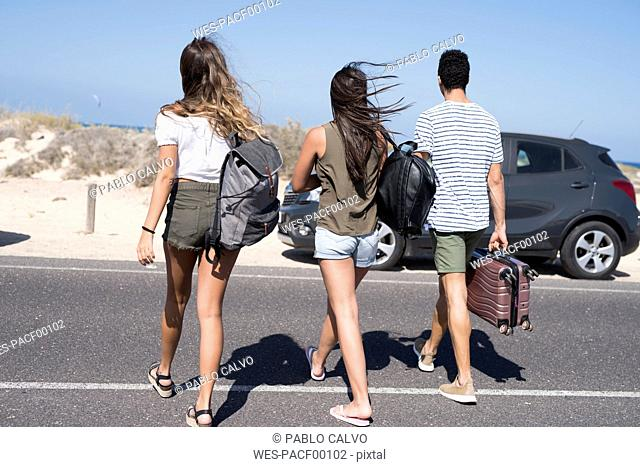Friends crossing road, carrying bags, going to the beach