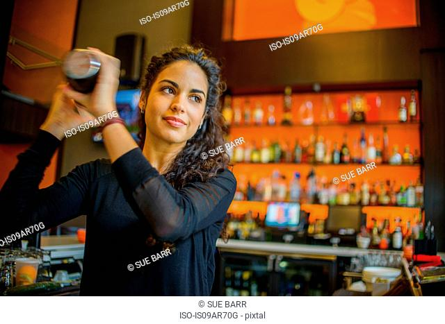 Young female bartender shaking cocktail shaker in cocktail bar