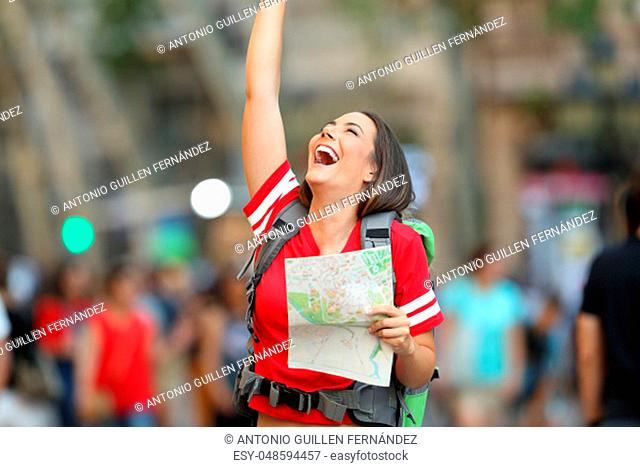 Joyful teen tourist holding a paper map and raising arms on the street