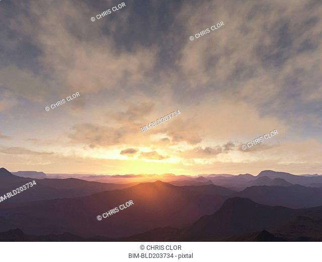 Sun rising over rural mountains