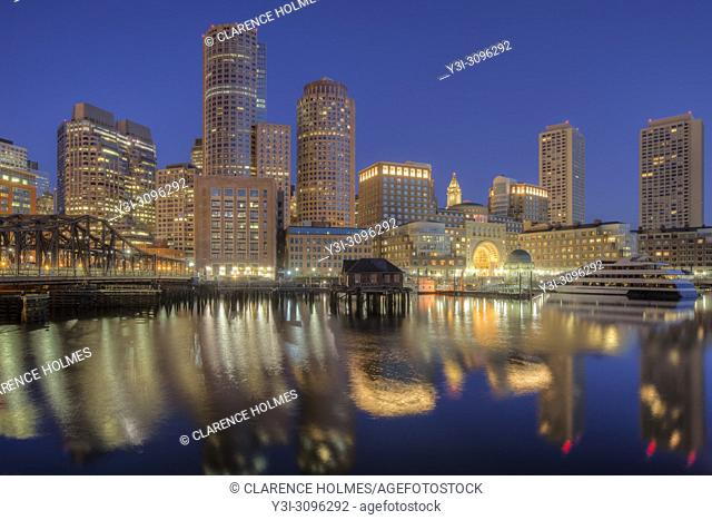 The skyline reflects off the still waters of the harbor in the last hour before sunrise as a new day begins in Boston, Massachusetts