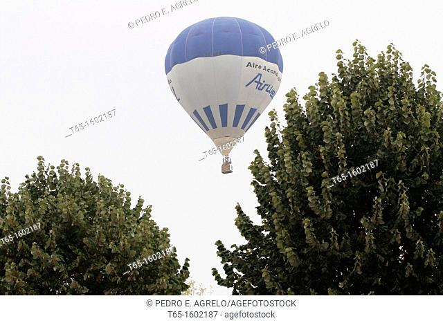 Hot air balloon flying over a park in the city of Lugo