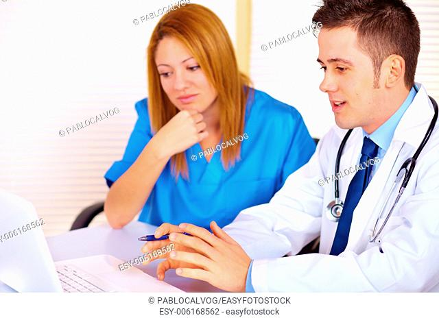 Portrait of a young doctor and a nurse talking and using a laptop on the office