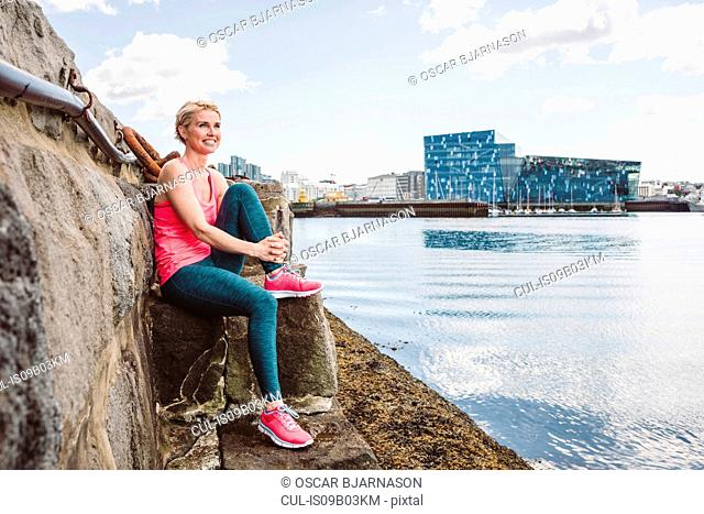 Female runner taking a break on sea waterfront, Reykjavik, Iceland
