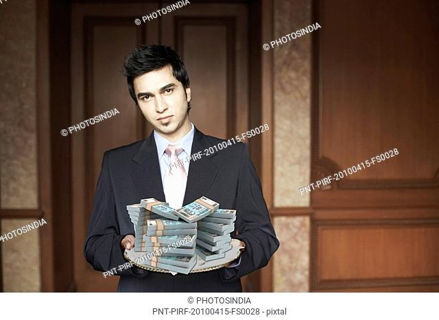 Businessman holding a platter full of Indian currency notes