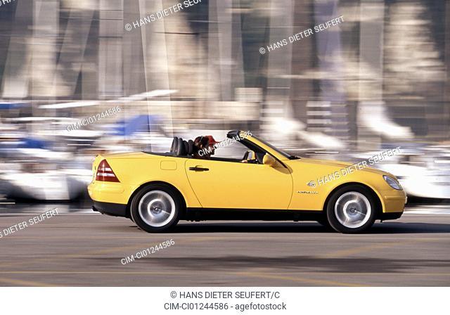 Car, Mercedes SLK, Convertible, model year 1996-2000, yellow, open top, driving, side view, Harbour, landsapprox.e, Summer