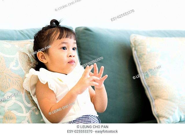 Adorable little girl sitting on couch at home