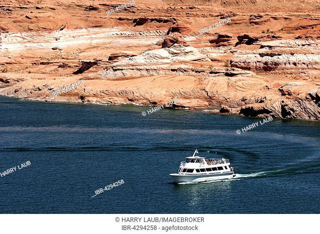 Red Navajo Sandstone cliffs at Lake Powell, excursion boat in Wahweap Bay, Page, Arizona, USA