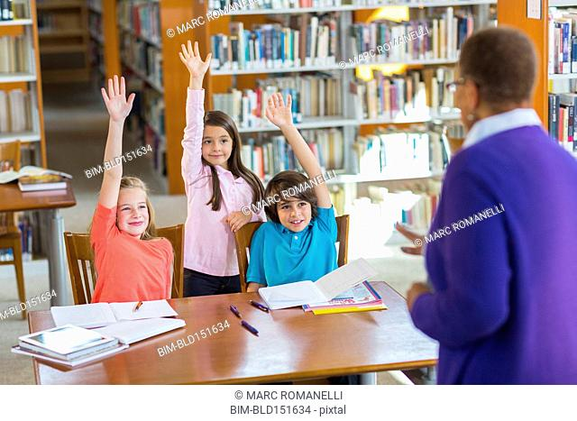 Students raising their hands in library
