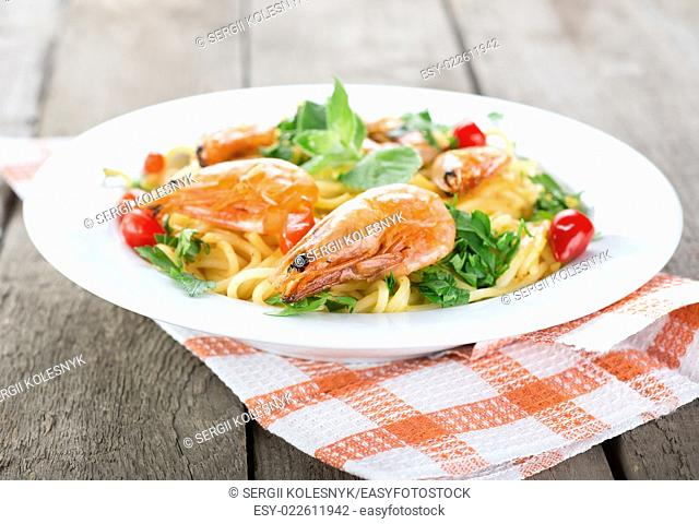 Macaroni with prawns and herbs on wooden table