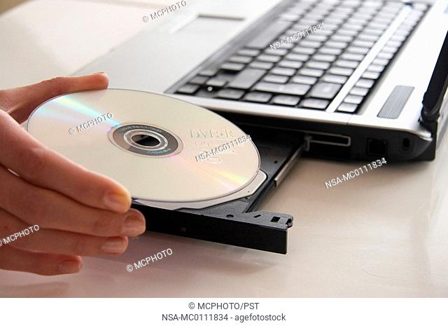 a hand putting a disc into a laptop