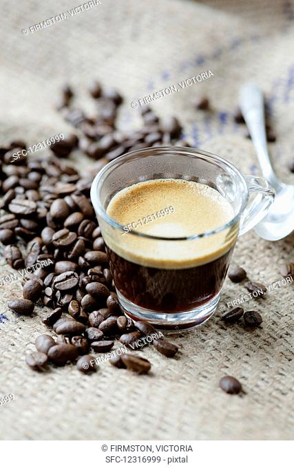 Espresso coffee with coffee beans and a teaspoon
