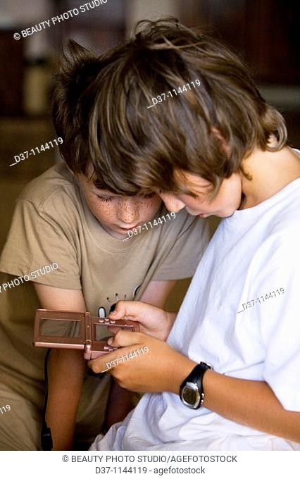 Two caucasian boys playing with a video game