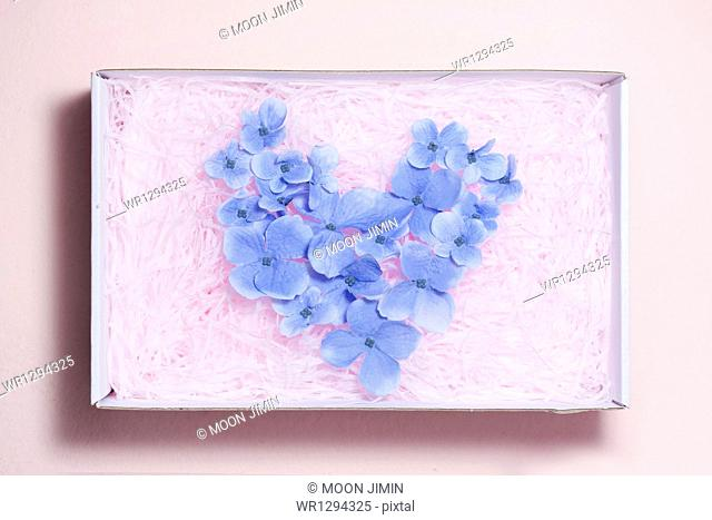 a heart shape inside a box filled with flowers