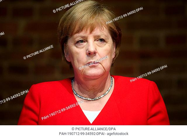 12 July 2019, Berlin: Federal Chancellor Angela Merkel (CDU) sits on the podium during a discussion on the 50th anniversary of the German Development Aid Act