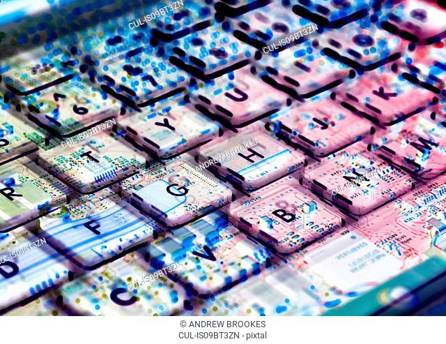 Multiple exposure of laptop computer showing keyboard and circuit board below