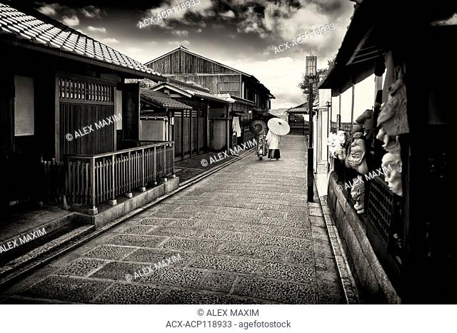 Black and white city scenery of a Couple with Japanese parasols wearing traditional kimono walking down an old street, Yasaka dori