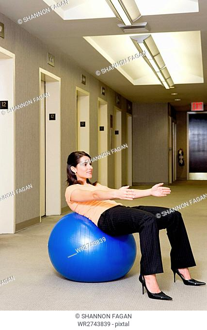 Female office worker using an exercise ball