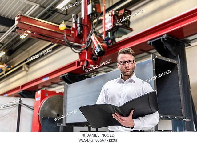 Businessman with folder standing on factory shop floor