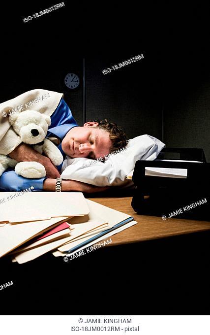 Man with stuffed animal sleeping on desk