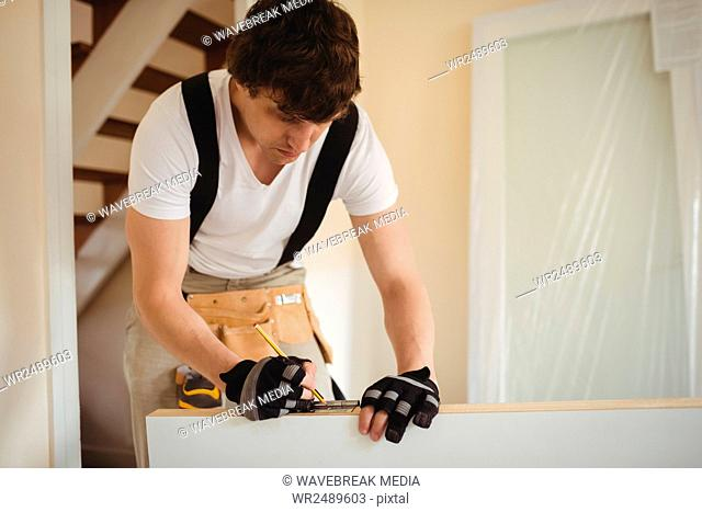 Carpenter measuring a wooden door Stock Photos and Images