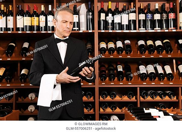 Waiter reading the label of a wine bottle