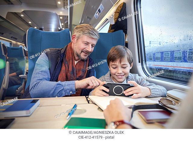 Father and son using smart phone on passenger train
