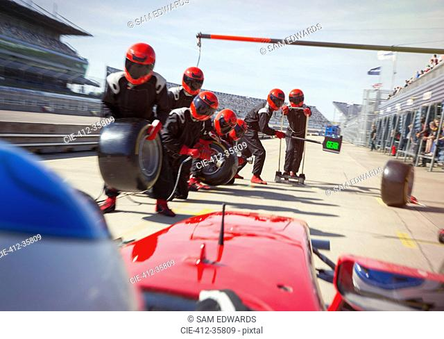Pit crew with tires ready for nearing formula one race car in pit lane