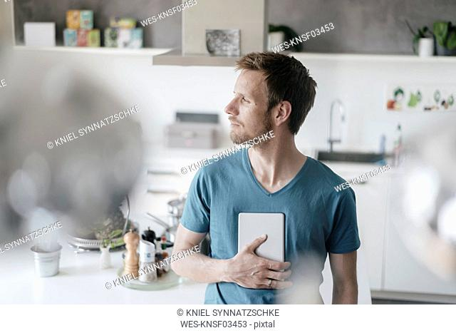 Man with tablet standing in the kitchen looking at distance