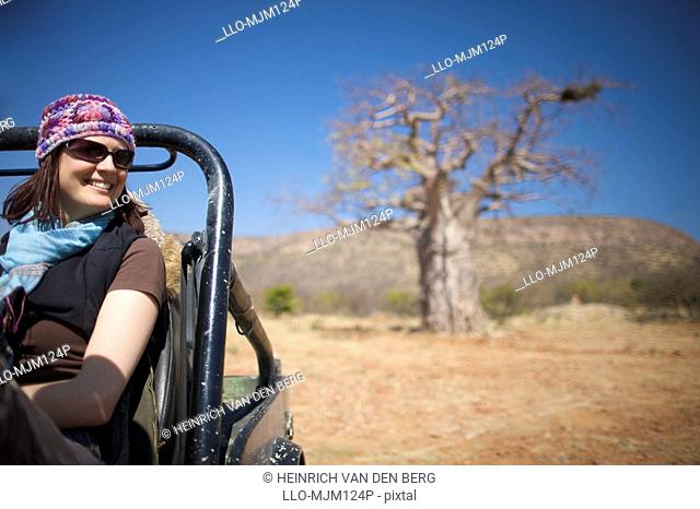 Young woman sitting in motor vehicle with Baobab tree in background, Kunene river area, Kaokoland, Namibia