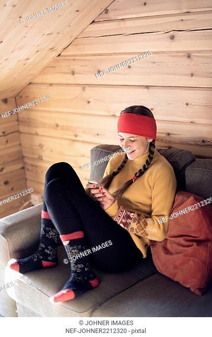 Teenage girl in log cabin