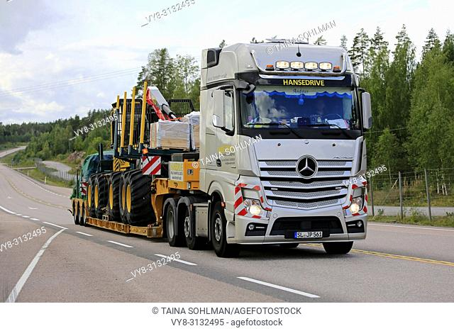 ORIVESI, FINLAND - AUGUST 27, 2018: Mercedes-Benz Actros semi trailer of Hansedrive transports forest machinery on highway in Finland on overcast day