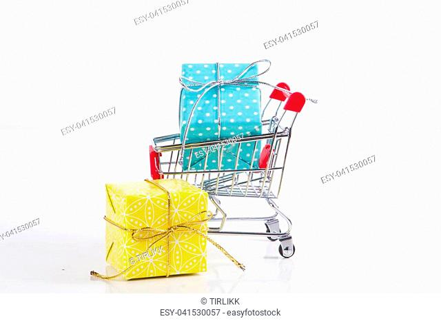 Trolley with gifts box on a white background. The concept of celebration and shopping. Selective focus