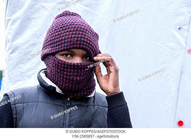 Calais, France. Male migrant inside The Jungle of Calais, wearing a mask to prtect himself against the cold