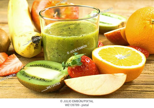 Natural smoothie surrounded by kiwi fruit on wooden base