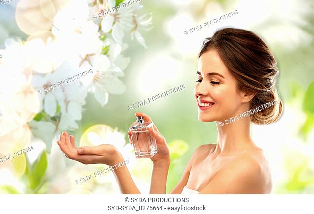 happy woman with perfume over cherry blossoms