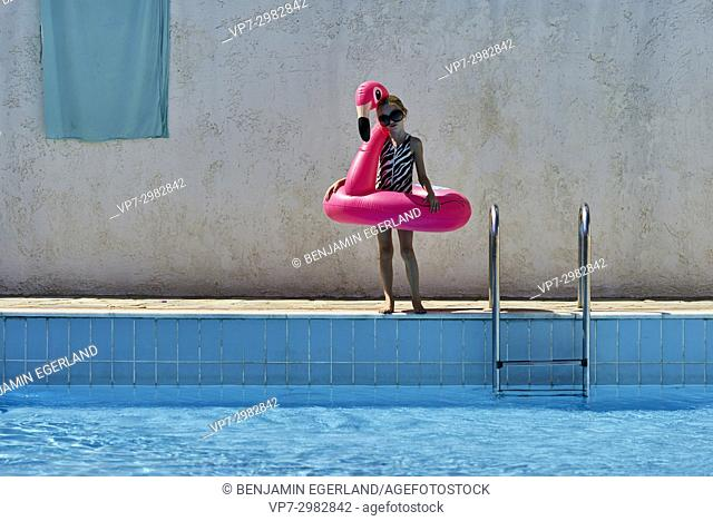 young child with swan rubber ring next to swimming pool, enjoying summer sun. Australian ethnicity