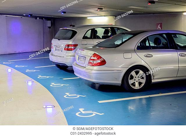 Cars parked on disabled reserved spaces in underground parking lot France