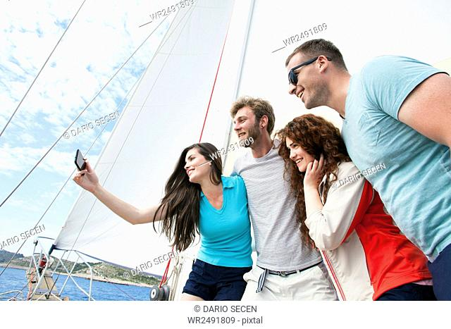 Friends taking self portrait with smartphone on sailboat