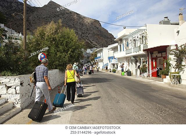Tourists with bags walking to the port in Kamares village, Sifnos Island, Cyclades Islands, Greek Islands, Greece, Europe