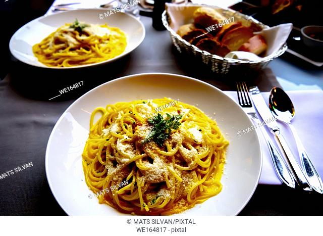 Carbonara Spaghetti and Bread on Table in Milan, Italy