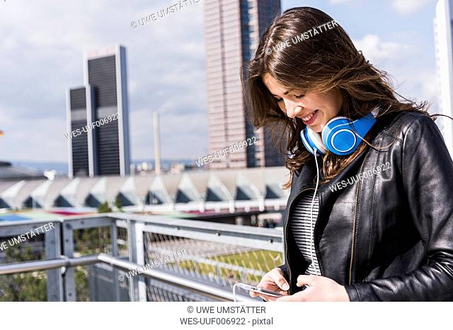 Young woman with headphones using smart phone