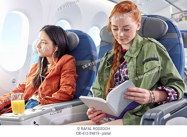 Young woman reading book on airplane