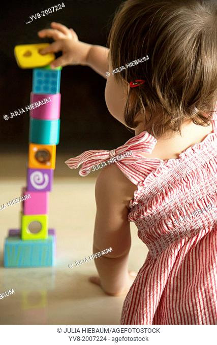 Baby girl skillfully balancing wooden blocks